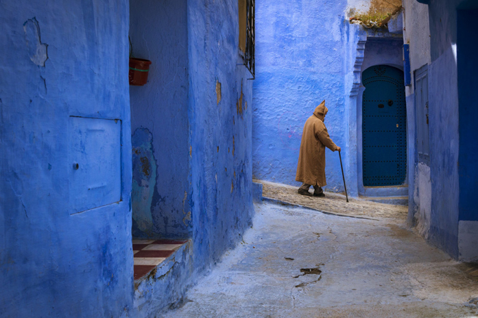 Standard picfair 05543760 chefchaouen morocco april 10 2016 moroccan man walking in a narrow street in the town of chefchaouen in morocco north africa 1120u preview only